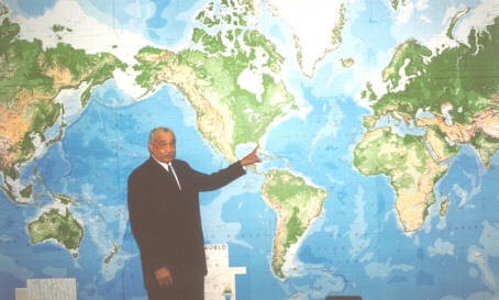 Chief Elder Walker Points To The Map In His Office To Show Where The AMA World Crusade Will Begin and End